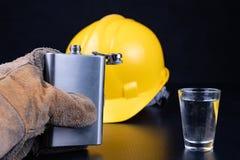 Ett skott av vodka och en flaska på en seminariumtabell Workwear och alkohol i seminariet av byggnadsarbetare fotografering för bildbyråer