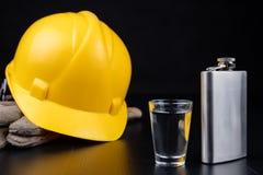 Ett skott av vodka och en flaska på en seminariumtabell Workwear och alkohol i seminariet av byggnadsarbetare arkivfoton