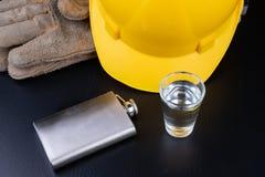 Ett skott av vodka och en flaska på en seminariumtabell Workwear och alkohol i seminariet av byggnadsarbetare arkivbilder