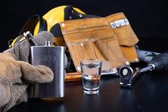 Ett skott av vodka och en flaska på en seminariumtabell Workwear och alkohol i seminariet av byggnadsarbetare arkivfoto