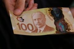 Ett slut av en man` s räcker upp den hållande kanadensiska räkningen för pengar $100 royaltyfri foto