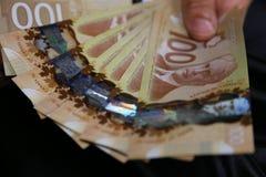 Ett slut av man's räcker upp hållande kanadensiska pengar royaltyfria foton