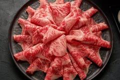 Ett slut specificerade upp bild av skivat japanskt wagyunötkött i en keramisk platta som var förberedd för Shabu Shab arkivfoto