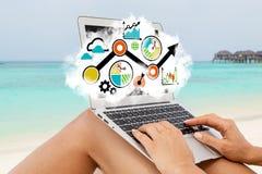 Ett slut upp av arbetsplatsen på stranden Den unga damen framkallar en affärsstrategi genom att använda en bärbar dator Arkivbild