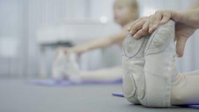 Ett slut upp av flickafot i gymshoes, medan göra gungan sideward under balettgruppen arkivfilmer