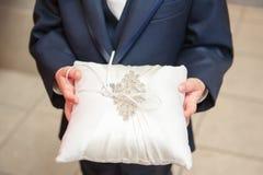 Ett slut upp sikt av en cirkelbärare som rymmer en brud- gifta sig kudde dekorerad med paljetter och brudens cirkel arkivfoton