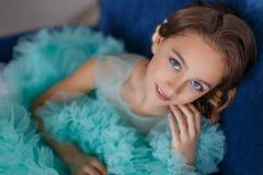 Ett slut upp ståenden av en härlig ung flicka med blåa ögon, med smink och frisyren i en frodig turkosklänning Arkivbild