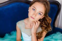 Ett slut upp ståenden av en härlig ung flicka med blåa ögon, med smink och frisyren i en frodig turkosklänning Royaltyfri Fotografi