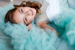 Ett slut upp ståenden av en härlig ung flicka med blåa ögon, sminket och frisyren i en frodig turkos klär att ligga Royaltyfria Bilder