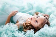 Ett slut upp ståenden av en härlig ung flicka med blåa ögon, sminket och frisyren i en frodig turkos klär att ligga Arkivfoto