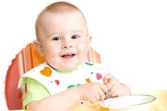 Ett småbarn lär att äta på hans egna Arkivfoto