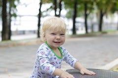Ett småbarn lär att gå nära bänkarna, litet barn Arkivbild