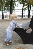 Ett småbarn lär att gå nära bänkarna, litet barn Royaltyfria Bilder