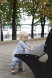 Ett småbarn lär att gå nära bänkarna, litet barn Royaltyfri Bild