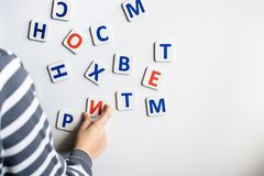 Ett småbarn lär bokstäverna av alfabetet Förberedelse för skola royaltyfri bild
