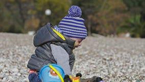 Ett småbarn ler in i kameran och spelar på stranden med leksaker stock video