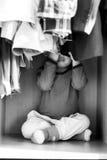 Ett småbarn nära garderoben med saker Arkivbilder