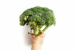 Ett småbarn rymmer broccoli i hans hand, honom är för ett sunt bantar arkivbild