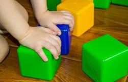 Ett småbarn som spelar med färgrika kuber, bygger ett torn, begreppet av den tidiga utbildningsförberedelsen för utvecklingen av fotografering för bildbyråer