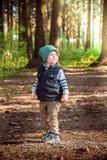 Ett småbarn står bara på skogkanten av en skog arkivfoton