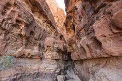 Ett smalt passerande between till gigantiska sandstenberg Arkivbild