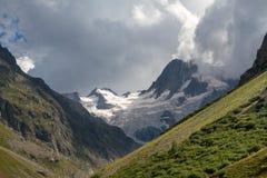 Ett snö täckt berg är solbelyst under orosmoln Royaltyfri Fotografi