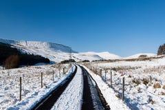 Ett snöig spårar blytak in mot snow capped berg fotografering för bildbyråer