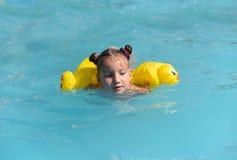 Ett soligt foto av en le liten flicka som tycker om att spela och att simma i den öppna pölen Arkivbilder