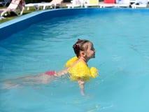 Ett soligt foto av en le liten flicka som tycker om att spela och att simma i den öppna pölen Royaltyfri Bild