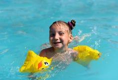 Ett soligt foto av en le liten flicka som tycker om att spela och att simma i den öppna pölen Royaltyfri Foto
