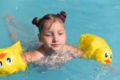 Ett soligt foto av en le liten flicka som tycker om att spela och att simma i den öppna pölen Fotografering för Bildbyråer