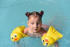 Ett soligt foto av en le liten flicka som tycker om att spela och att simma i den öppna pölen Arkivbild
