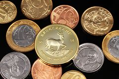 Ett sortiment av brasilianska mynt på en svart reflekterande bakgrund med ett södra - afrikan ett guld- krugerrandmynt för uns royaltyfri bild