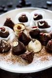 Ett sortiment av fina choklader i vit, mörker, och mjölkar choklad på den vita plattan Royaltyfria Bilder