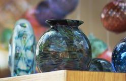 Ett sortiment av hantverkare blåste exponeringsglasobjekt och prydnader Arkivfoton