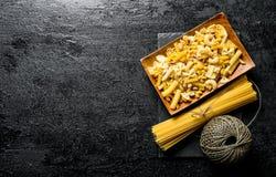 Ett sortiment av olika typer av pasta som ?r torra p? en platta med, tvinnar arkivfoto