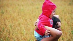 Ett spädbarn med mamman som spelar och ler i fält med vete arkivfilmer