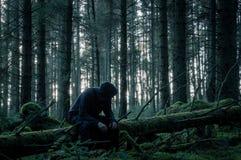 Ett spöklikt ensamt med huva diagram som sitter på en dold inloggning för mossa en skog i vinter Med dämpad redigera arkivbild