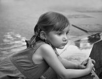 Ett stads- slut upp den allvarliga ståenden av lite flickan nära den granit- balustradväggen av en springbrunn Arkivfoton