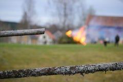 Ett staket med en brand i bakgrunden arkivfoto