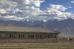 Ett stenhus med moment på en bakgrund av snöig berg arkivfoton