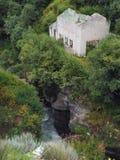 Ett stenhus utan ett tak står på kanten av en hög klippa ovanför floden under den överflödande grönskan av skogen Royaltyfri Foto