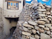 Ett stenstaket, ett murverk av gråa ovalstenar, i bakgrunden ett vitt tibetant hus med ett traditionellt fönster, i exponeringsgl Royaltyfri Fotografi