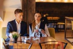 Ett stilfullt par dricker morgonkaffe p? kaf?t, de unga aff?rsm?nnen och freelancersna fotografering för bildbyråer