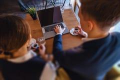 Ett stilfullt par dricker morgonkaffe p? kaf?t och arbetar med en b?rbar dator, unga aff?rsm?n och freelancers royaltyfri foto