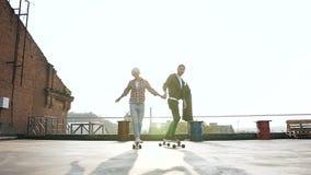 Ett stiligt ungt par som rymmer händer som skidar på en skateboard på taket av en modern byggnad Pojke och flicka som skidar på arkivfilmer