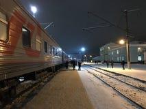 Ett stopp av det långdistans- drevet på en snöig afton för vinter under ljus av lyktor Lopp med de ryska järnvägarna för företag arkivbilder