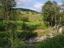 Ett storartat landskap på ett hus på ett backeanseende på foten av ett grönt berg Arkivbild