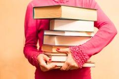 Ett stort antal böcker i händerna Royaltyfri Fotografi