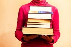 Ett stort antal böcker i händerna Arkivbild